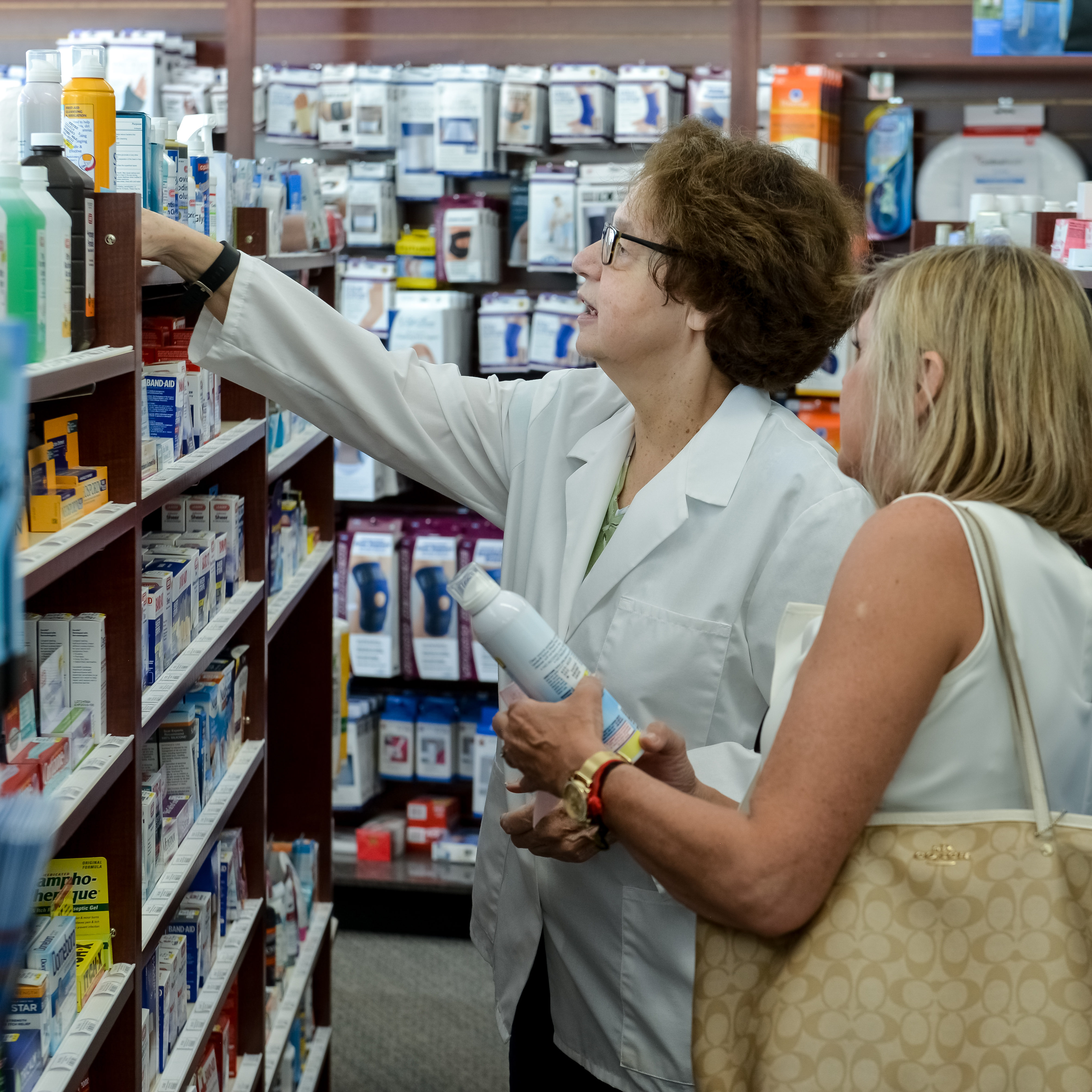 Keyes Drug pharmacist assisting customer in selecting medical product.
